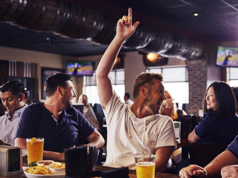 Sports bar and grill Big Whiskey's guests celebrating local happy hours on gameday.