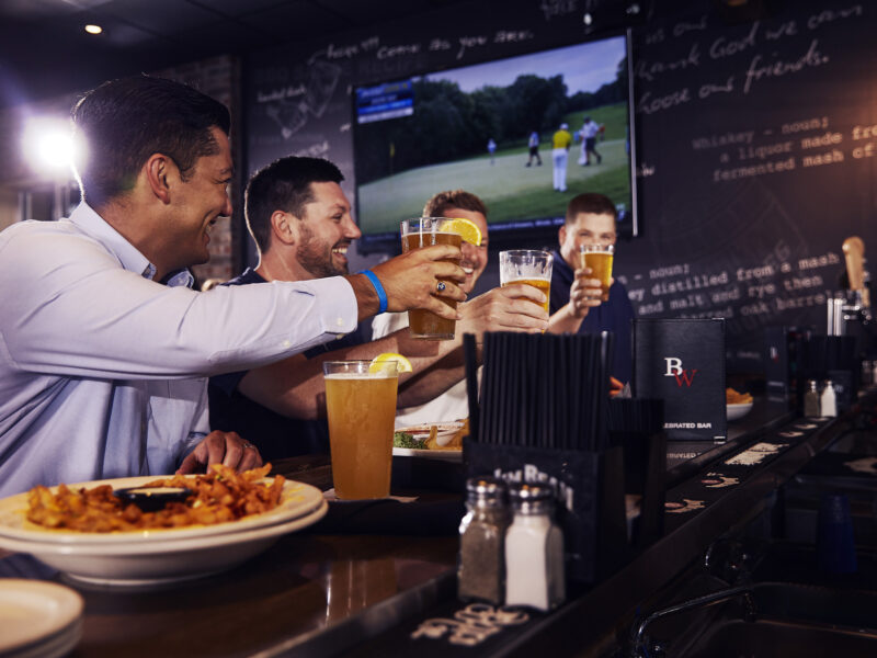 Friends celebrate the local happy hours specials on sports bar and grill Big Whiskey's gameday menu.