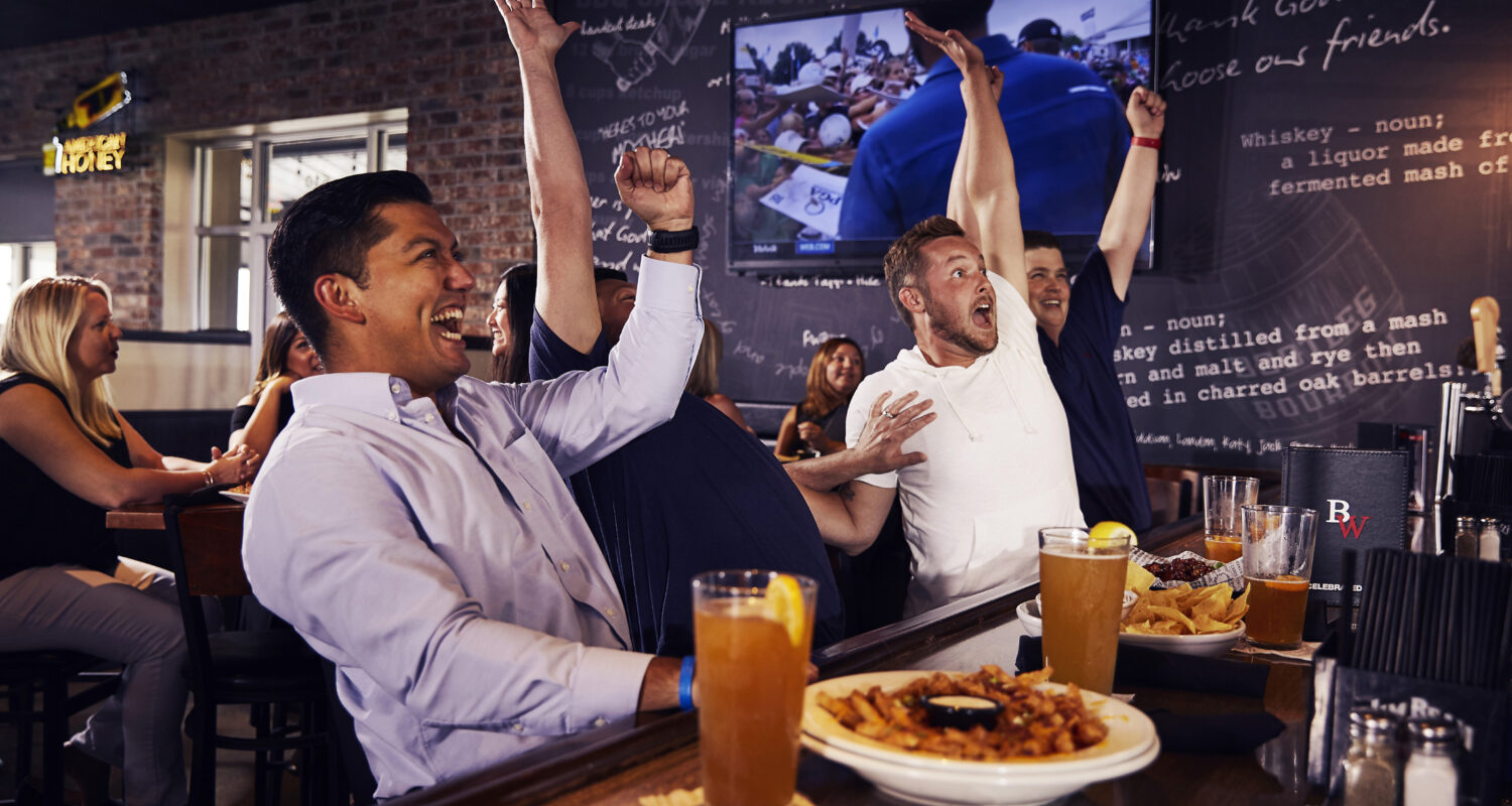 Excited fans at sports bar and grill Big Whiskey's celebrate a score on gameday.